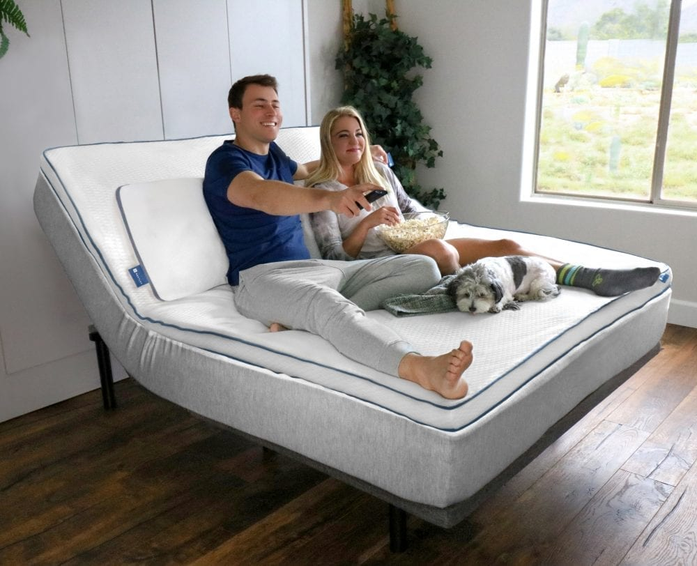 A couple happily watching TV on their Nestled topper and motion base with their cute dog