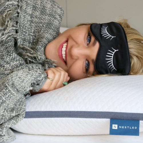 A smiling woman who is very happy to be laying on a comfortable Nestled pillow