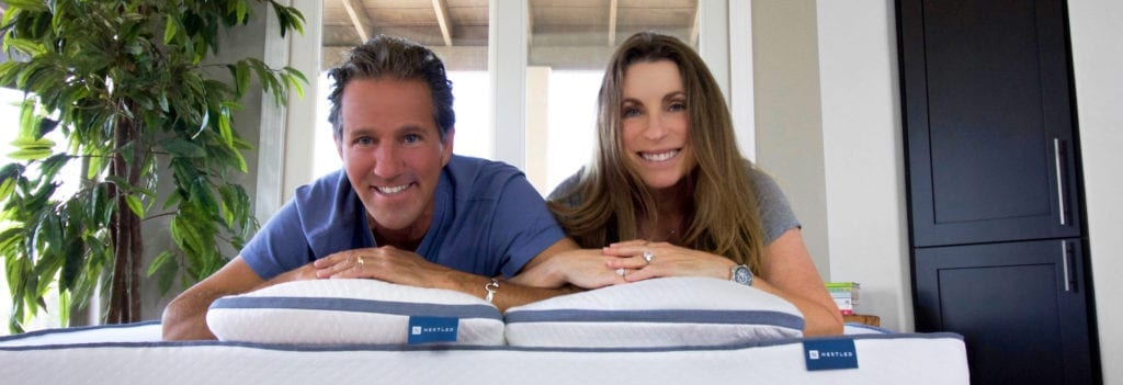 Parents laying on top of their Nestled organic mattress topper and Nestled pillows