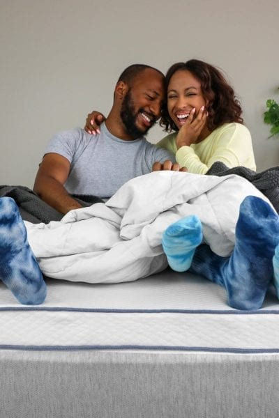 A happy couple enjoying their Nestled latex mattress topper