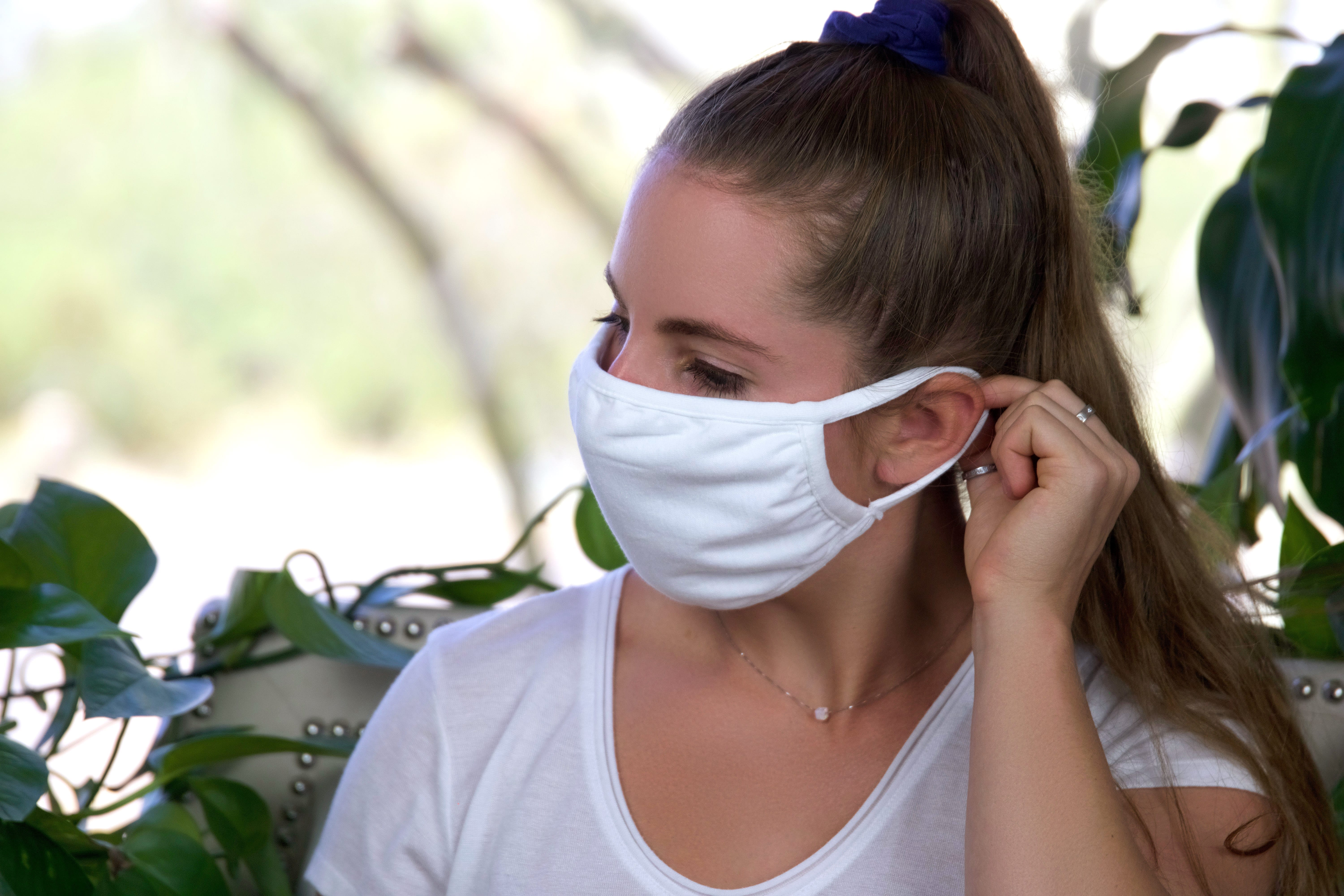 Woman adjusting her Naturally Nestled mask covering.