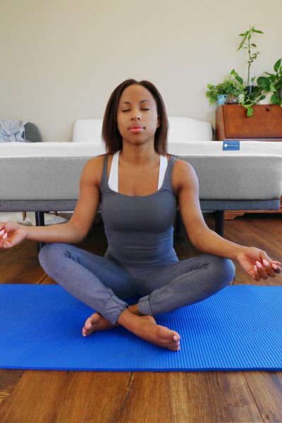 woman sitting and meditating in front of a bed