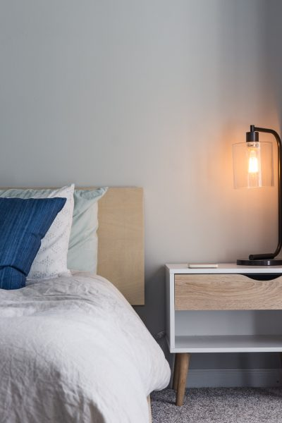 a bed with a side table and lamp beside it